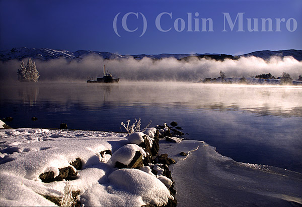 Like a ghost ship, a survey vessel cruises through winter fog across Loch Ness