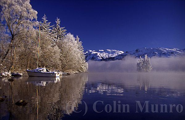 Frozen birch trees and snow-capped mountains reflected on the still waters of Loch Ness, Highlands, Scotland, UK.