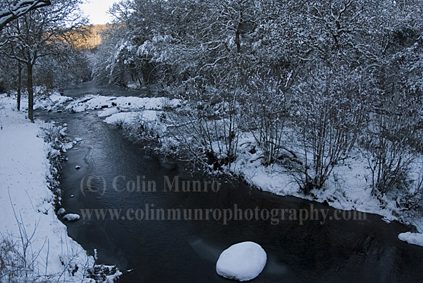 Snow-covered upland oak woodland along banks of the River Teign,  Dunsford Wood, South Devon, UK.