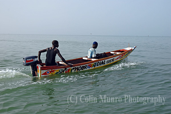 M'bour, Senegal. Two Senegalese fishermen head out to sea in a small pirogue (traditional wooden canoe).  Image MBI000909.