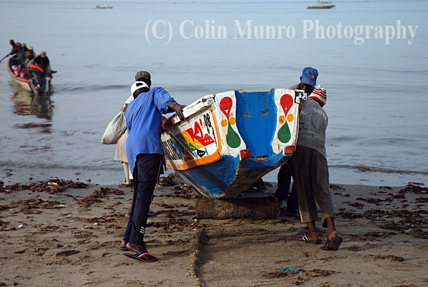Fishing canoe,  or pirogue, being lanched off beach on wooden rollers, M'bour,  Senegal.  Image MBI000628