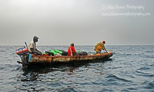 A fishing canoe, or pirogue, with a broken down engine, drops anchor and waits for a passing boat to tow them to shore, Senegal, off M'bour, West Africa