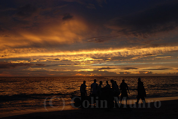 M'bour, Senegal. Fishermen haul a small fishing pirogue (wooden canoe) up on to the beach at sunset.  Image MBI000739