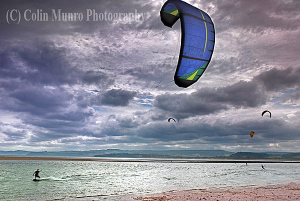 Kite surfer against a dramatic sky, surfing the Exe Estuary between Pole Sand sandbar and Exmouth Beach, Exmouth, Devon, England. Image MBI000660.