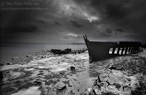 The wreck of an old wooden boat trapped in ice covered mudflats is silhouetted against an ominous sky. Exe Estuary near Turf Locks, Devon, UK. Fine Art Prints for sale. Colin Munro Photography. www.colinmunrophotography.com