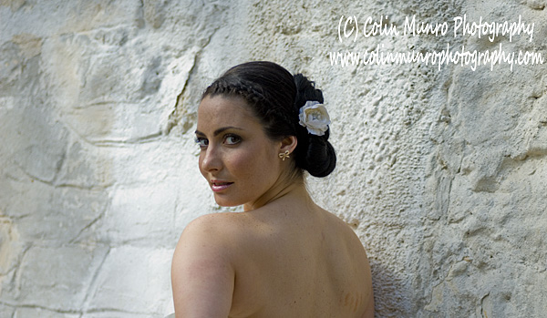Head and shoulders shot of Spanish or Italian looking girl with a white rose in her hair, looking backwards over her shoulder, against a whitewashed wall. Colin Munro Photography.