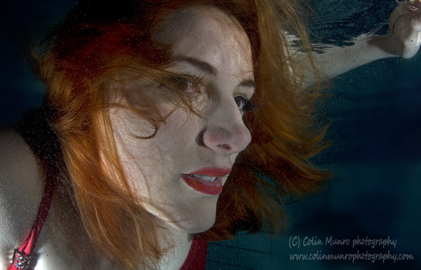 close up of fae and eyes of a Red haired girl in a red dress underwater. Colin Munro Photography