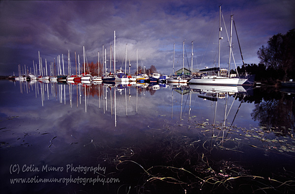 Yachts mirrored on the still waters of Exeter Canal, by the Turf Locks, Exe Estuary, with dark clouds reflected on a cold winter's day. Colin Munro Photography.