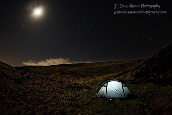 The glow from a lantern inside a dome tent on a starry, moonlit night on Dartmoor.  Colin Munro Photography.