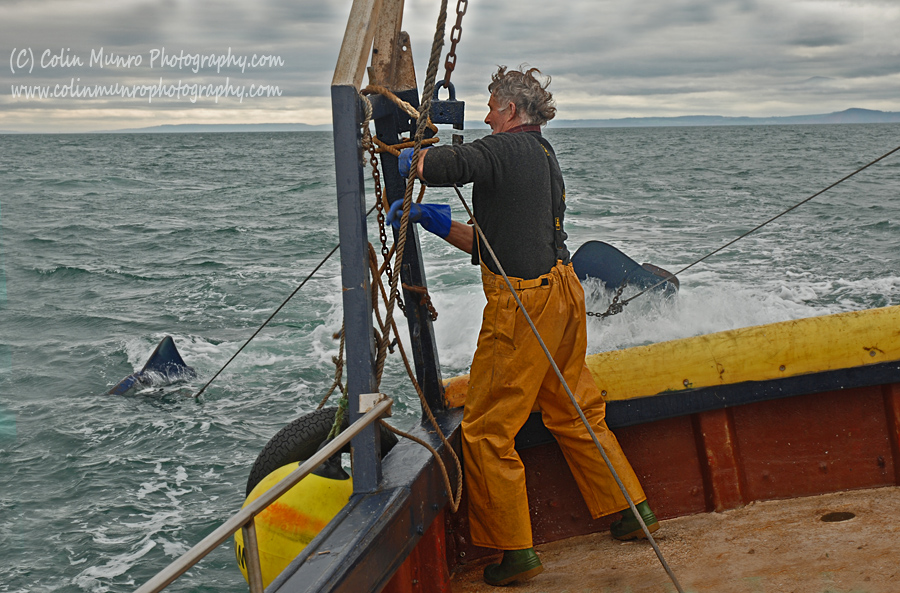 A fisherman lifts the steel wire warps, that tow the trawl net, in to blocks at the stern of the trawler. Colin Munro Photography