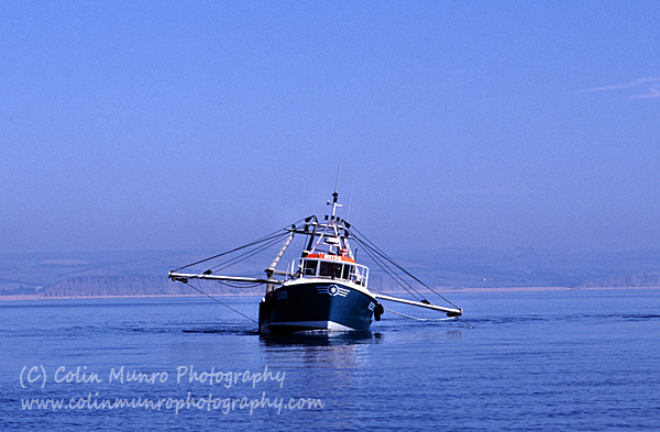Scallop dredger heeling over as the dredges on one side catch fast on the seabed. Lyme Bay. Colin Munro Photography.