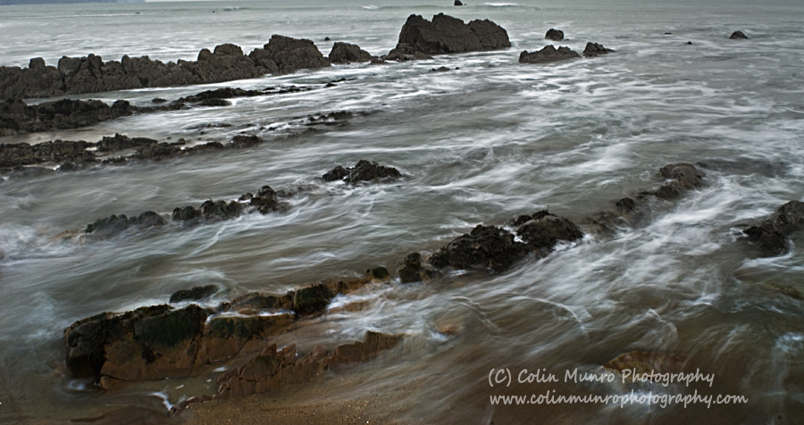 Waves spill over rocks, Widemouth Bay, North Cornwall. Colin Munro Photography