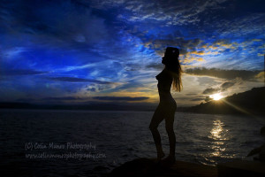 A girl silhouetted by the setting sun. The backlighting from the sun catches on the edges of her hair, creating a pleasing backlighting. Colin Munro Photography