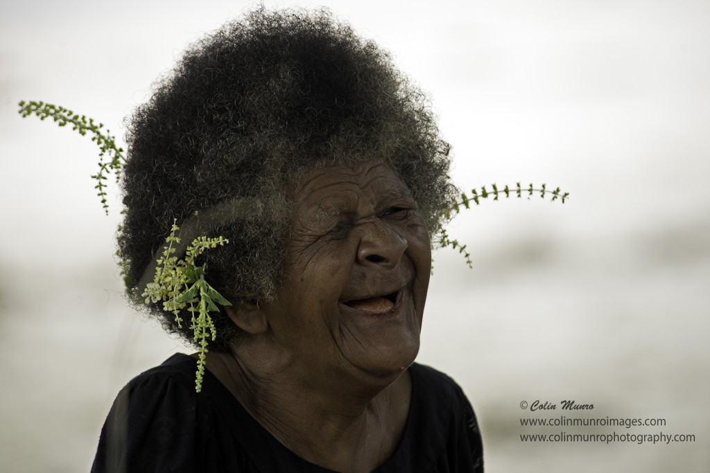 An old lady weaving pandanus leaves laughs as she works. Suau Island, Milne Bay Province, Papua New Guinea. Colin Munro Photography © Colin Munro