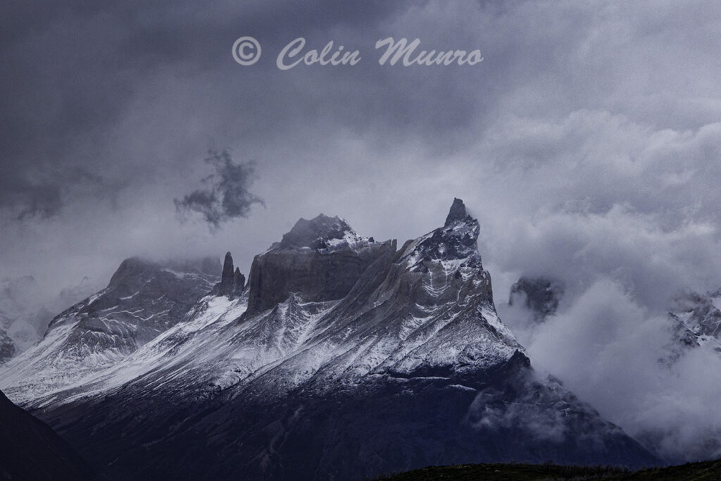 Torres del Paine mountain peaks among dark, brooding clouds. Patagonia, Chile. Fine Art Print by Colin Munro Photography