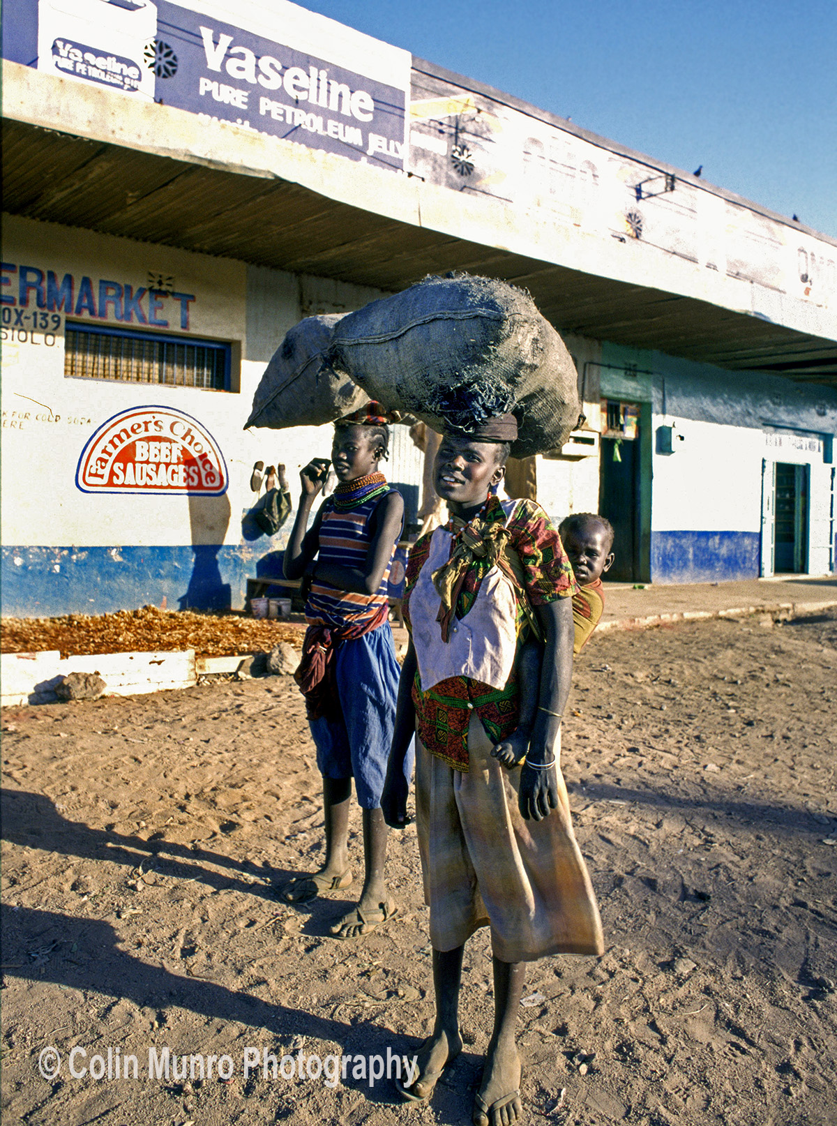 Isiolo, Kenya. 1980s. two girls carry sacks of charcoal to sell. www.colinmunrophotography.com