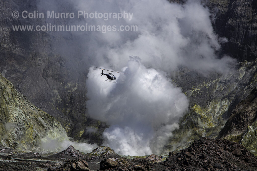 A tour helicopter flies close to the steam plume emanating from the crater lake, White Island andesite stratovolcano, Bay of Plenty, New Zealand North Island, 2017.